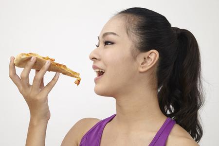 Chinese woman enjoying eating pizza