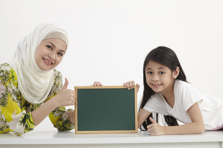 mothher and daughter holding small blackboard