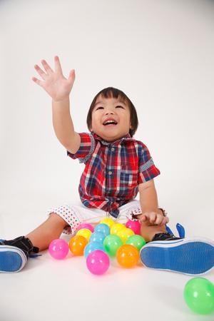chinese boy raising his arm try to pick up something Standard-Bild - 122523116