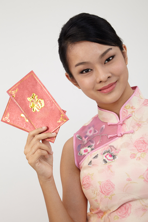 chinese young woman holding ang paw for happy chinese new year 版權商用圖片