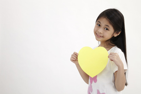 kid holding yellow heart shaped card on the white background