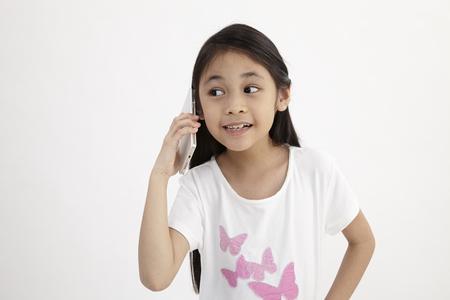 Infanzia e tecnologia. Bambina sveglia che utilizza smart phone. Isolato su bianco. Archivio Fotografico