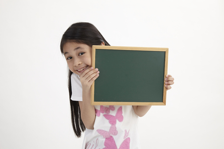 Cute little girl holding a chalkboard, isolated on white