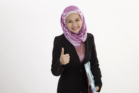 malay woman wearing  business suit holding document files with thumb's up Stockfoto