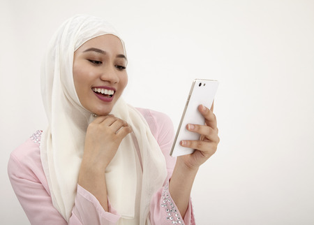 malay woman with tudung  reading a message on  cell phone Stock Photo