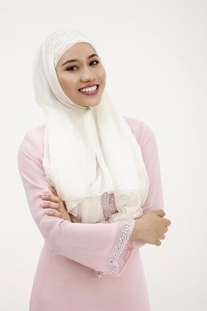 confidient malay woman with pink baju kurung looking at camera