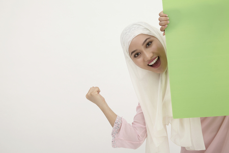 malay woman with tudung,behind of the green placard