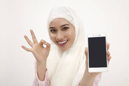 portrait of malay woman holding phone with ok sign