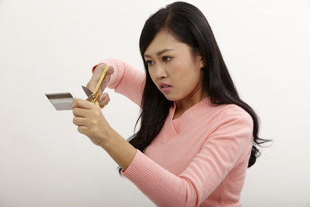 asian holding a pair of scissors cutting credit card