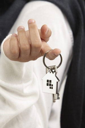 close up of  woman holding a house shape keyring