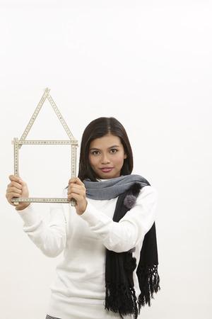 malaysische Frau, die ein faltbares Lineal in einer Hausform hält Standard-Bild