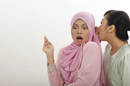Two teenage girls gossiping on the white background