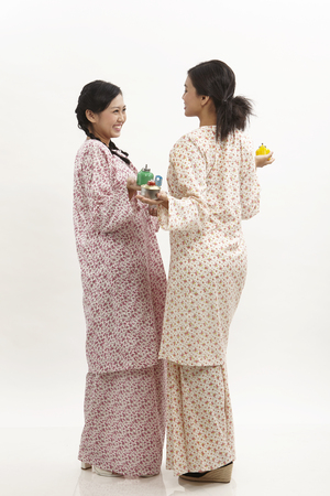 two malay woman wearing baju kedah holding pelita on the white background