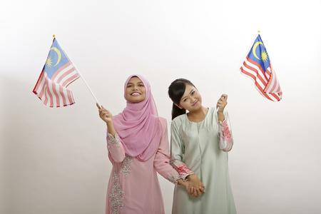 two malay  women holding malaysia flag