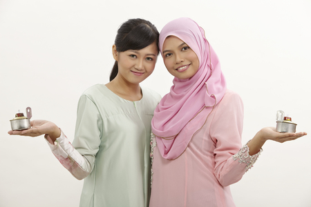 two malay women holding oil lamp or pelita