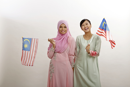 two malay  women holding malaysia flag