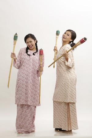 two malay woman wearing baju kedah holding pelita on the white background