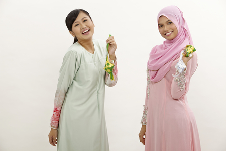 two malay women holding decoration ribbon ketupat