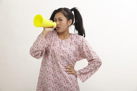 malay woman with baju kedah holding a mega phone shouting 版權商用圖片