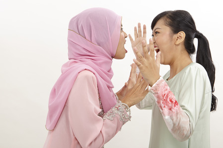 Two girls friends standing on white background discontent and having an argument