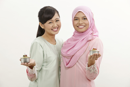 two malay women holding oil lamp or pelita