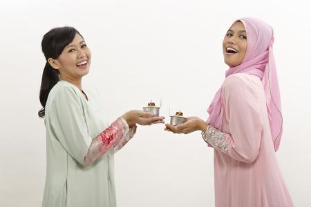 two malay women holding oil lamp or pelita Stock Photo