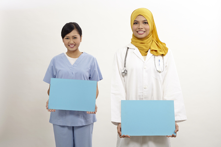 asian female doctor and nurse holding placard