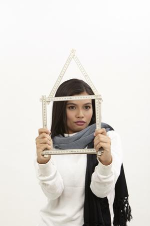 malay woman holding a folderable ruler form a house shape Stockfoto