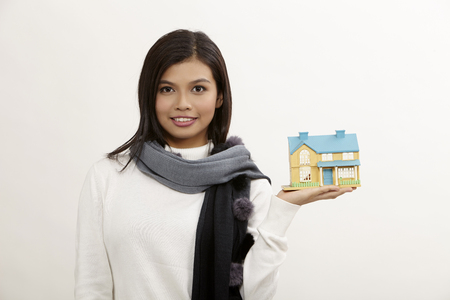 asian woman holding a white model house