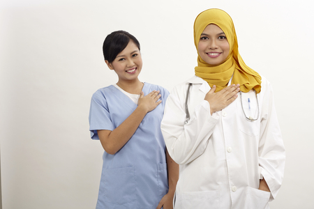 asian nurse and doctor with welcome hand sign on the white background