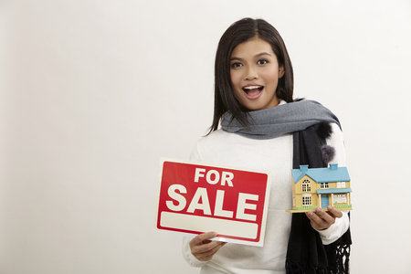 asian woman holding a white model house and for sale sign