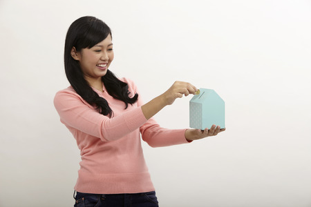 woman holding a house shape coin box on the white background