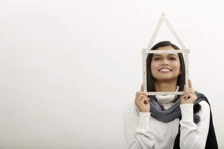 malay  woman looking through the house frame, over white background
