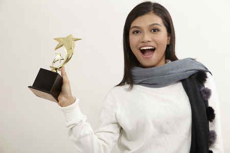 malay woman holding a star trophy on the white bakground