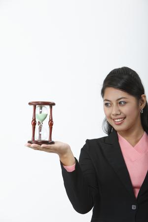 Jeune femme tenant un sablier