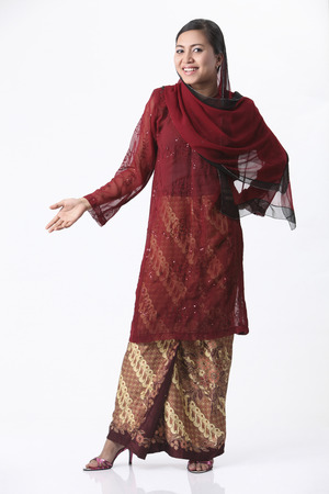 Malay woman with red baju kurung isolated on the white background. 스톡 콘텐츠