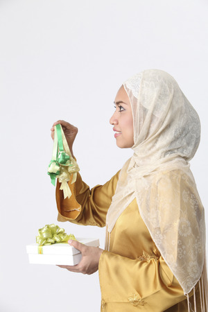 Malay woman holding ketupat with a gift on her hand. 스톡 콘텐츠