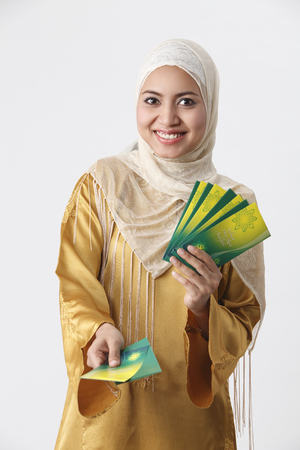 Malay woman giving out green packets.