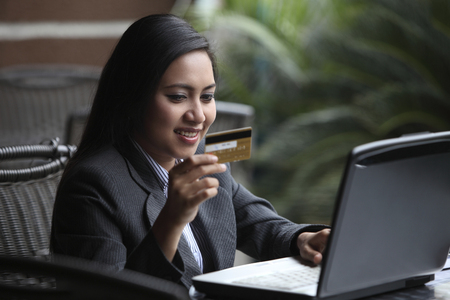 Woman holding a credit card while using a laptop. Banco de Imagens