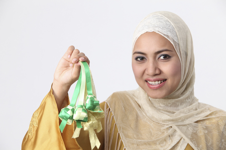 Malay woman holding decorative items.