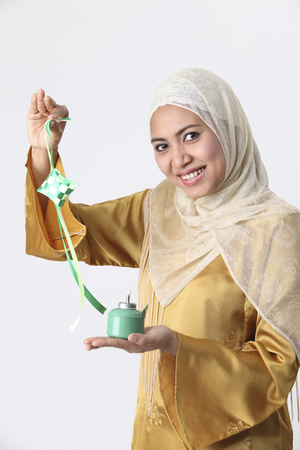 Malay woman holding pelita and ketupat.
