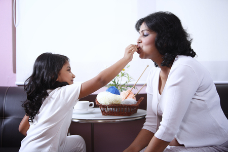 Generosity of children, cute little girl is feeding her mother strawberries