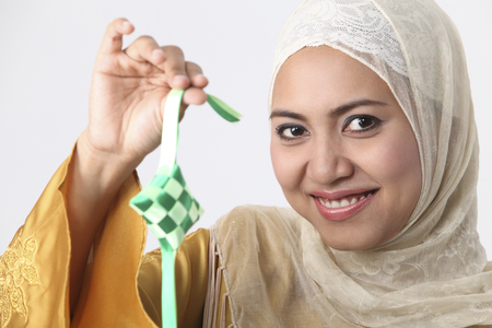 Malay woman holding a ketupat. 스톡 콘텐츠