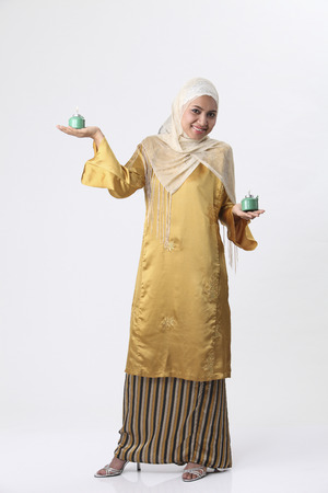 Malay woman holding a pelita. 스톡 콘텐츠