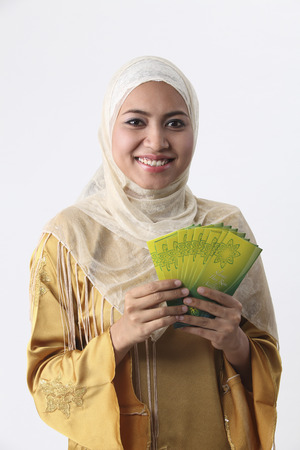 Malay woman giving away green packets.