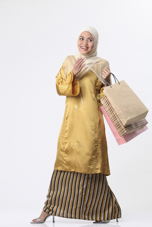 Malay woman holding shopping bags. Imagens