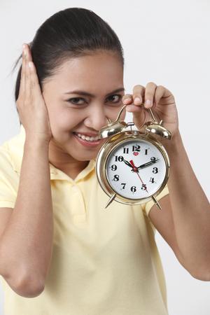 Malay woman holding an alarm clock.
