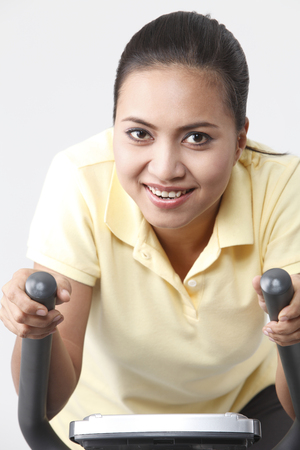 Malay woman cycling on the exercise bike.