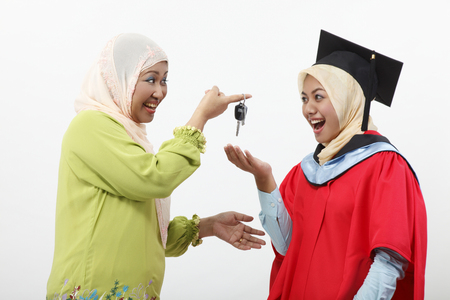 Senior woman giving car key to her daughter
