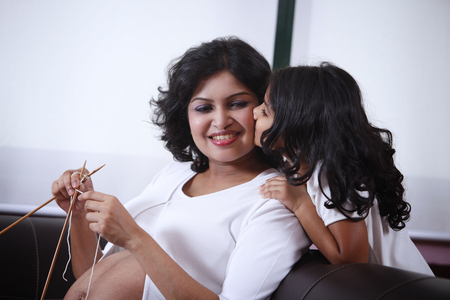 A Girl Kissing Mothers Cheek While Mother Is On Knitting Work. Stock Photo